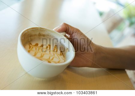 Woman Hand Holding Coffee Cup Caramel Macchiato Hot Of Coffee Drink On Wooden Table In The Cafe