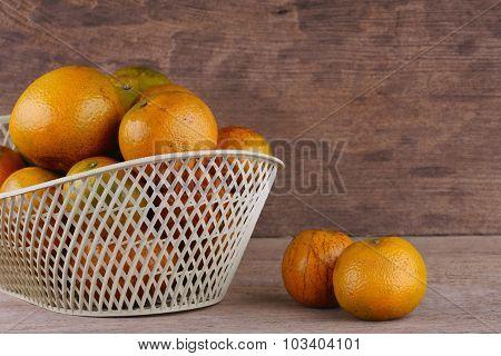 Orange Fruit In White Basket On Wood Table Background