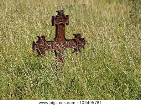 Isolated Rusty Iron Cross At Ancient Graveyard