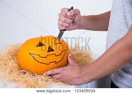 Close Up Of Man With Knife Carving Pumpkin Jack-o-lantern For Halloween