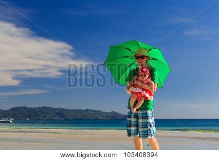 father and daughter with umbrella on beach vacation