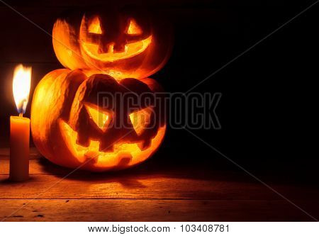 Selective Focus Bright Light In Pumpkins Stack Together On Wood Background With Candle By Dark Light