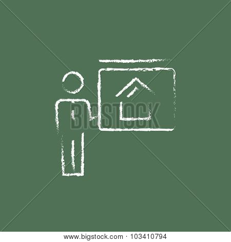 Real estate agent showing the house hand drawn in chalk on a blackboard vector white icon isolated on a green background.