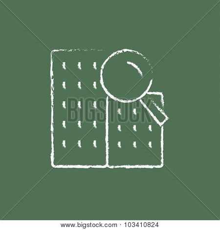 Condominium and magnifying glass hand drawn in chalk on a blackboard vector white icon isolated on a green background.