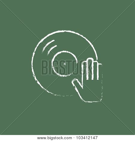 Dj hand with disc hand drawn in chalk on a blackboard vector white icon isolated on a green background.