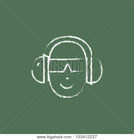 Man in headphones hand drawn in chalk on a blackboard vector white icon isolated on a green background.