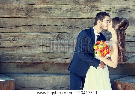 Just Married Couple Kissing Each Other On Wooden Background