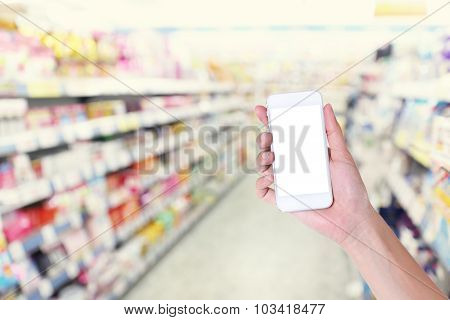 Woman Hand Showing Smart Phone With Warehouse Background