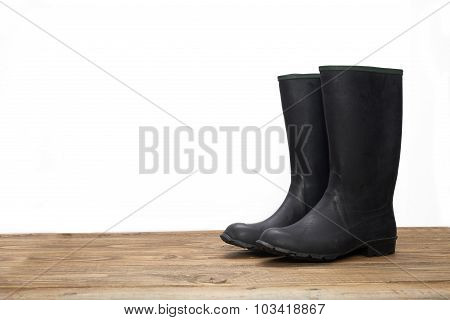 Plastic Waterproof Boots On A Wooden Table