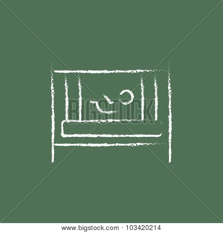 Baby in the crib hand drawn in chalk on a blackboard vector white icon isolated on a green background.