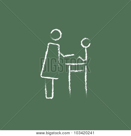 Woman taking care of the baby hand drawn in chalk on a blackboard vector white icon isolated on a green background.