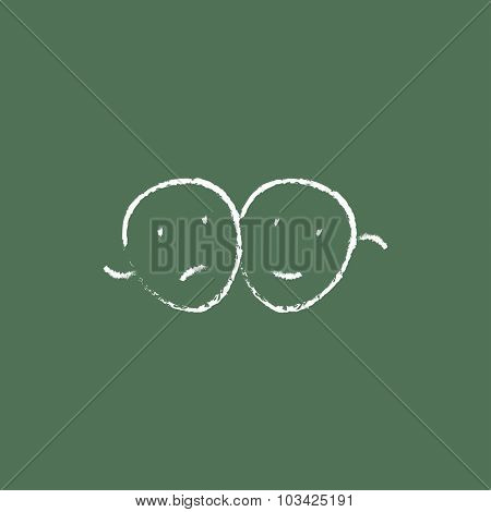 Two theatrical masks hand drawn in chalk on a blackboard vector white icon isolated on a green background.