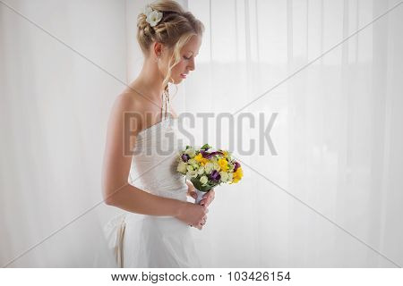 Bride looking down at her wedding bouquet