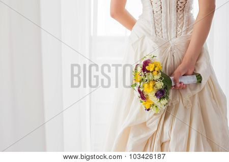 Bride holding her wedding flowers behind her back