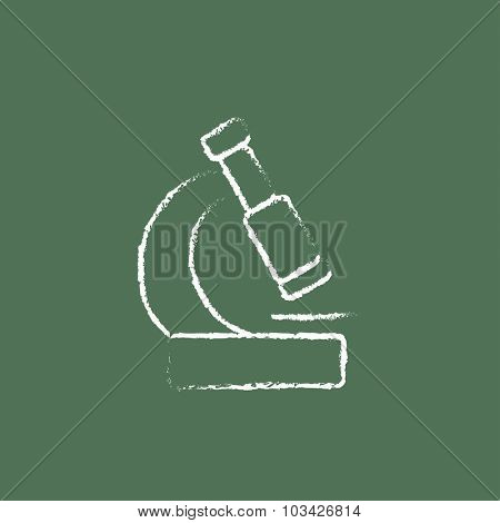 Microscope hand drawn in chalk on a blackboard vector white icon isolated on a green background.