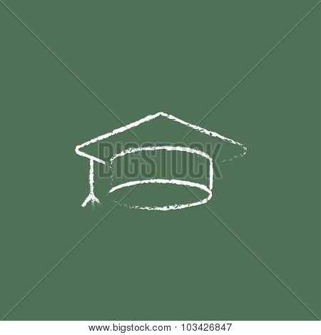 Graduation cap hand drawn in chalk on a blackboard vector white icon isolated on a green background.