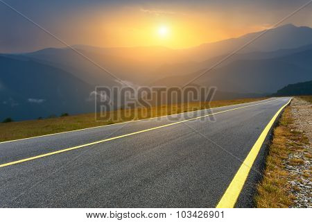 Driving On Empty Mountain Road At Sunset