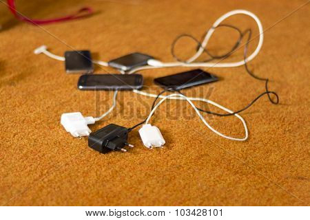 Phone Chargers on the orange carpet floor