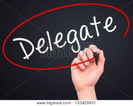 Man Hand writing Delegate black marker on visual screen.