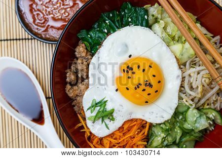 Korean cuisine, beef  Bibimbap in a bowl pot on wooden table