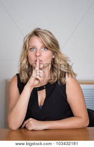 Blond Young Woman At Office With Finger In Her Mouth