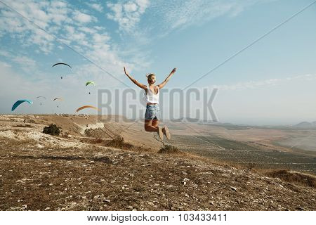 Young Women Joyfully Jumping With Glider In Background