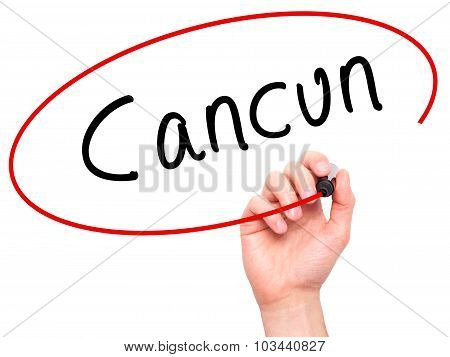 Man Hand writing Cancun with black marker on visual screen.