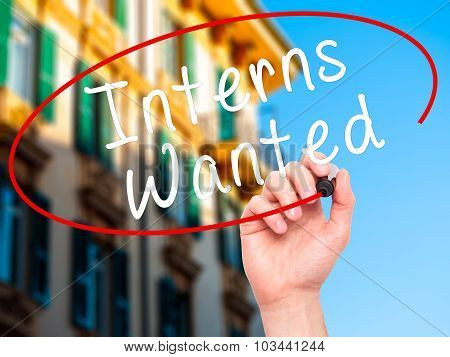 Man Hand writing Interns Wanted with black marker on visual screen