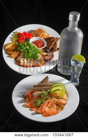 Close-up view of bottle of vodka and glasses with Marinated vegetables and sliced meat  decorated with parsley and dill, also appetizer - salted salmon and bread at the plate standing on black