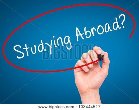 Man Hand writing Studying Abroad? black marker on visual screen.