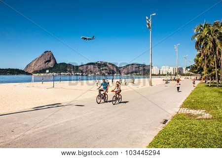 RIO DE JANEIRO, BRAZIL - APRIL 28, 2015: Young Brazilian couple rides their bicycles along the boardwalk at Botafogo Beach on April 28, 2015 in Rio de Janeiro , Brazia.
