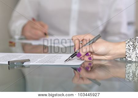Female hand signing formal paper