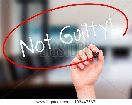 Man Hand writing NOT GUILTY with black marker on visual screen.