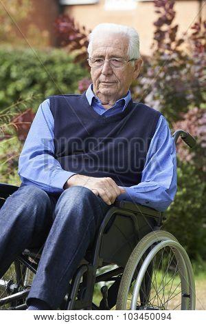Depressed Senior Man Sitting Outdoors In Wheelchair