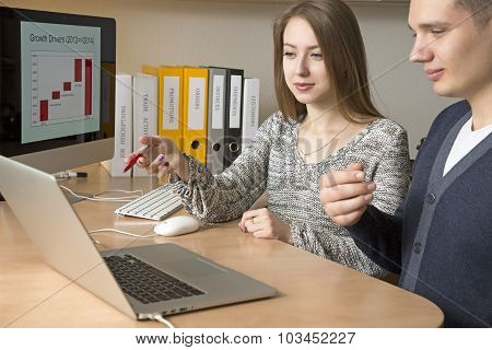 Office workers discuss the task sitting at the desk and gesturing