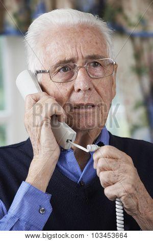 Worried Senior Man Answering Telephone At Home