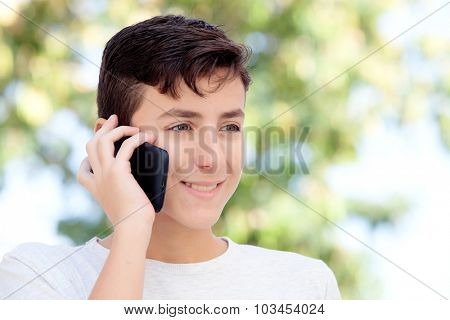 Teenage boy talking on the mobile in the street