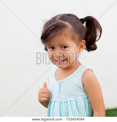 Funny little girl with pigtails saying Ok outdoor