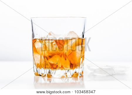 Glass of cold whiskey on whote surface with ice