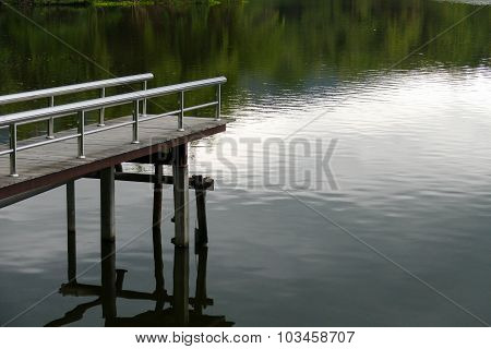 Pier At The Waterside Of The Pond In The Evening