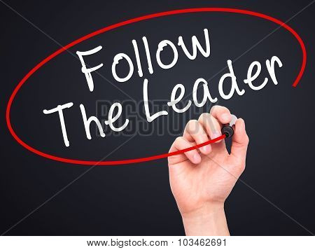 Man Hand writing Follow The Leader with black marker on visual screen.