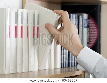 Choosing book Hand of man in white sleeve cuff shirt taking up grey book