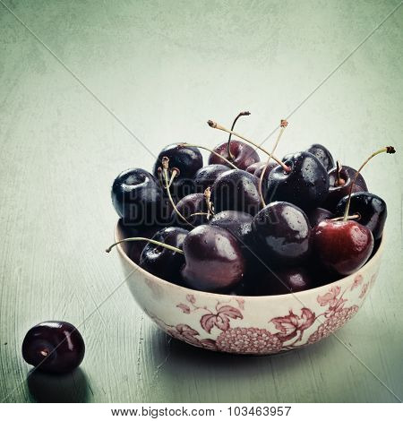 Fresh cherries in vintage floral bowl with grunge textured and green vintage antique aged filter