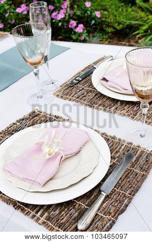 Table setting with napkin and rustic trimmings in the garden