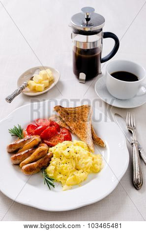Scrambled eggs with fried tomatoes, pork sausages chipolata and wholemeal toast, full breakfast served with coffee