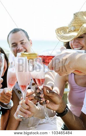 Pouring champagne sparkling wine into glasses outdoors at a beach with happy smiling friends