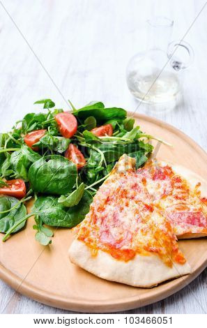 Pizza dinner with healthy side salad, salami and cheese topping