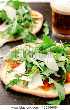 Fresh oven baked mini pizzas topped with rocket and cheese, served with ale