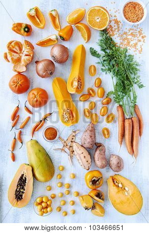 Collection of fresh orange toned vegetables and fruit raw produce on white rustic background, pumpkin butternut carrot papaya pawpaw capsicum pepper sweet potato cherry tomatoes chilli orange