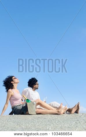 Mix race couple relaxing on their honeymoon holiday with champagne, clear blue sky plenty of copy space